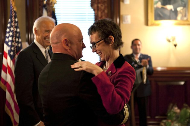 In this image released by the White House, Navy Capt. Mark Kelly hugs his wife Rep. Gabrielle Giffords, D-Ariz., after he received the Legion of Merit from Vice President Joe Biden during Kelly's reti