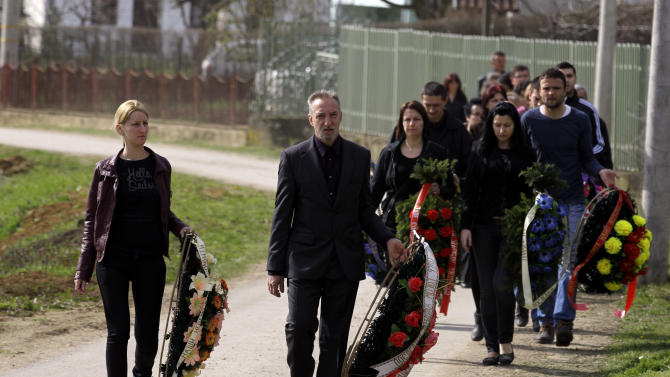 Mourners arrive to a cemetery prior to a mass funeral for the victims of a shooting in the village of Velika Ivanca, some 50 kilometers (30 miles) southeast of Belgrade, Serbia, Friday, April 12, 2013. The village of Velika Ivanca is preparing for the funerals of thirteen victims of a shooting that happened on Tuesday, April 9, 2013. Ljubisa Bogdanovic, a local and a Yugoslav wars veteran, went from house to house on April 9 in the village at dawn, cold-bloodedly gunning down his mother, his son, a 2-year-old cousin and ten other neighbors. (AP Photo/ Darko Vojinovic)