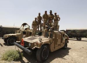 Members of the Iraqi security forces pose as they guard volunteers who have joined the Iraqi Army to fight against the predominantly Sunni militants, who have taken over Mosul and other Northern provinces, travelling in army trucks, in Baghdad