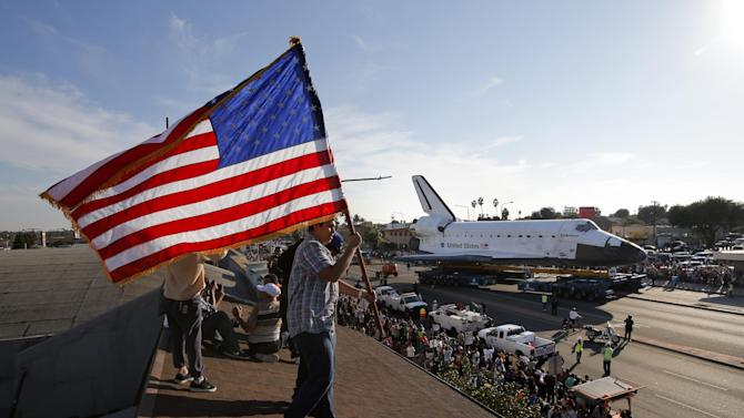 Roni Lopez, center, holds an American flag as the Space Shuttle Endeavour slowly moves along city streets on a 160-wheeled carrier in Los Angeles, Saturday, Oct. 13, 2012 towards the California Science Center museum. (AP Photo/Jae C. Hong)