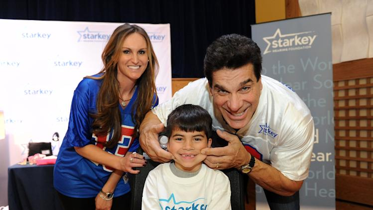 Dr, Trevi Sawalich of Starkey Hearing Foundation poses with Jacob Chadock and actor Lou Ferrigno with his new hearing aid on Saturday, Feb. 2, 2013 in New Orleans. (Photo by Cheryl Gerber/Invision for Starkey Hearing Foundation/AP Images)