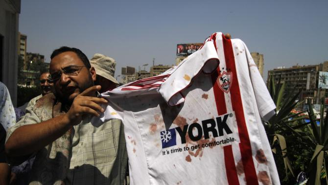 """A man displays a bloodied shirt of ousted President Mohamed Morsi's supporter outside a local hospital in Cairo. Egypt, Monday, July 8, 2013. Egyptian soldiers and police opened fire on supporters of the ousted president early Monday in violence that left dozens of people killed, including one officer, outside a military building in Cairo where demonstrators had been holding a sit-in, government officials and witnesses said. """" .(AP Photo/Nasser Shiyoukhi)"""