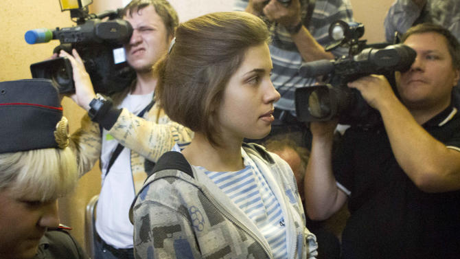 """Nadezhda Tolokonnikova, center, a member of feminist punk group Pussy Riot is escorted to a court room in Moscow, Russia, Friday, July 20, 2012. The trial of feminist punk rockers who chanted a """"punk prayer"""" against President Vladimir Putin from a pulpit inside Russia's largest cathedral started in Moscow on Friday amid controversy over the prank that divided devout believers, Kremlin critics and ordinary Russians. (AP Photo/Misha Japaridze)"""