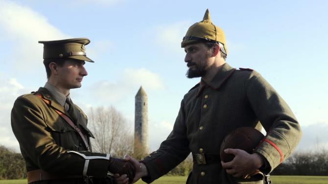 Figurants shake hands onto the pitch prior to a soccer match to mark the centenary of the legendary football match between the German and Allied troops on the Western Front during the Christmas Truce of 1914, at the Flanders Peace Field in Mesen