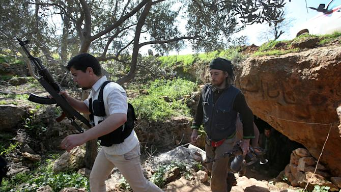 Free Syrian Army fighters from the Knights of the North brigade leave one of their caves to reconnaissance a Syrian army forces base of al-Karmid, at Jabal al-Zaweya, in Idlib province, Syria, Wednesday, Feb. 27, 2013. Syrian warplanes carried out airstrikes on rebels trying to storm a police academy outside Aleppo on Wednesday, while jihadi fighters battled government troops along a key supply road leading to the southeastern part of the city, activists said. (AP Photo/Hussein Malla)