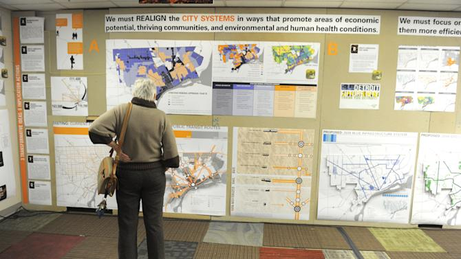 """Mary Egan Price, of Detroit, looks at a vast display for  """"Detroit Future City""""  presented  during a news conference at the DWPLTP Homebase on Wednesday, Jan. 9, 2013. The presentation introduces a framework for future decision making for the city. (AP Photo/The Detroit News, Max Ortiz)"""
