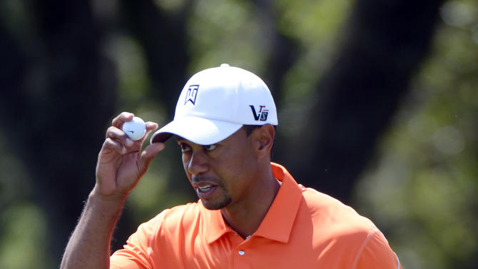 Tiger Woods holds up his ball and tips his hat to the gallery after sinking a putt on the first hole during the second round of the Arnold Palmer Invitational golf tournament, Friday, March 22, 2013, in Orlando, Fla. (AP Photo/Phelan M. Ebenhack)