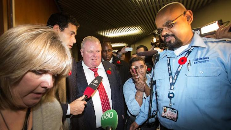 Mayor Rob Ford (C) leaves his office at Toronto City Hall as he is surrounded by media on November 8, 2013 in Toronto, Ontario