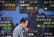 A man walks past an stock prices screen in the window of a securities company in Tokyo. Asian markets fell on Monday after declines in the US and Europe on disappointing American jobs data that raised fresh concerns about the world's biggest economy