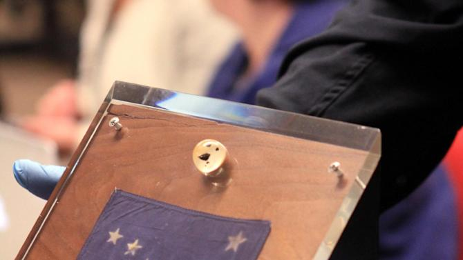 Alaska State Museum curator of collections Steve Henrikson shows a plaque containing an Alaska flag below moon rocks encased in acrylic glass on Thursday, Dec. 6, 2012, at Anchorage School District offices in Anchorage, Alaska. President Richard Nixon presented the display to Alaska Gov. Keith Miller in 1969 after the Apollo 11 moon mission. The display disappeared from a museum after an arson fire in 1973 but was returned to the state Wednesday after settlement of a lawsuit. (AP Photo/Dan Joling)
