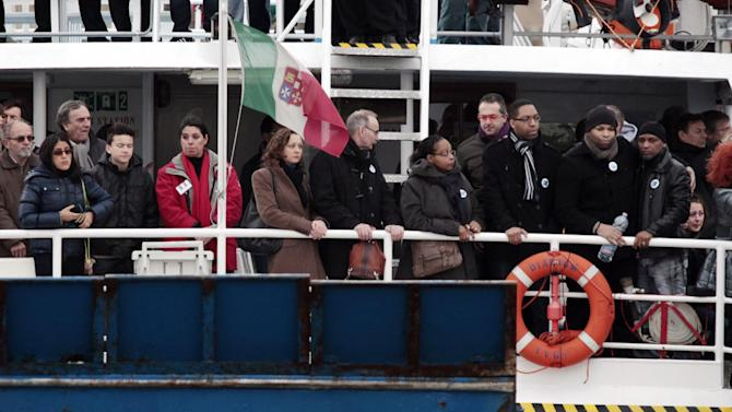 Relatives of the 32 victims of the Costa Concordia shipwreck, aboard a ferry approach the ship off the Tuscan Island Isola del Giglio, Italy, Sunday, Jan. 13, 2013. Survivors of the Costa Concordia shipwreck and relatives of the 32 people who died marked the first anniversary of the grounding Sunday. The first event of Sunday's daylong commemoration was the return to the sea of part of the massive rock that tore into the hull of the 112,000-ton ocean liner on Jan. 13, 2012 and remained embedded as the vessel capsized along with its 4,200 passengers and crew. (AP Photo/Gregorio Borgia)