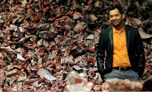 Pakistani artist Imran Qureshi poses next to his work on September 23, 2013 during the opening of his exhibition in Rome
