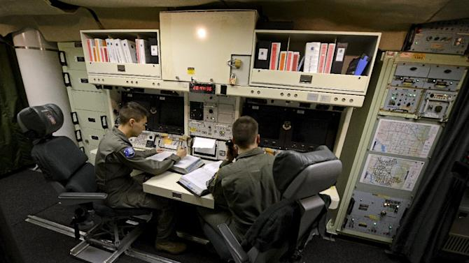 In this photo taken June 24, 2014, 2nd Lt. Oliver Parsons, right, and 1st Lt. Andy Parthum check systems in the underground control room where they work a 24-hour shift at an ICBM launch control facility near Minot, N.D. The crew is responsible for controlling and launching the 10 nuclear-tipped Minuteman 3 missiles located in remote launch sites under their command. (AP Photo/Charlie Riedel)