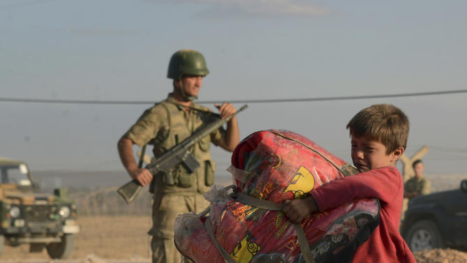 Turkish soldiers stand guard as a Syrian refugee boy carries his belongings at the border in Suruc, Turkey, late Saturday, Sept. 20, 2014. Several thousand Syrians, most of them Kurds, crossed into Turkey on Friday to find refuge from Islamic State militants who have barreled through dozens of Kurdish villages in northern Syria in the past 48 hours.(AP Photo)