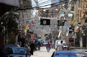 Electric cables and Islamist flags hang over a street …