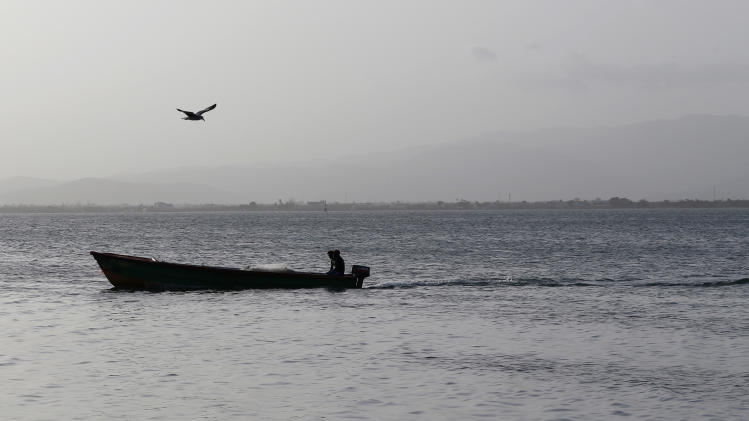 "In this June 6, 2013 photo, fishermen navigate their boat back to shore near the historic town of Port Royal in southeastern Jamaica. Across the Caribbean, governments and fishing communities are beginning to understand that such ""no-take"" zones can help rebuild severely depleted fish stocks and make coastal ecosystems more resilient to a warming planet. (AP Photo/Andres Leighton)"