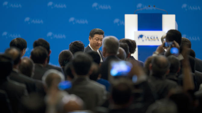 China's President Xi Jinping, center back, walks to his seat as he arrives at the opening ceremony of the annual Boao Forum in Boao, in southern China's Hainan province, Sunday, April 7, 2013. (AP Photo/Alexander F. Yuan)