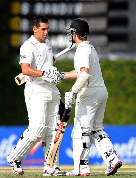 New Zealand captain Ross Taylor (L) is congratulated by teammate Kane Williamson after scoring a century (100 runs) during the first day of the second and final Test match between Sri Lanka and New Ze