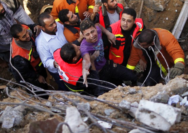 "Members of the Palestinian Civil Defense help a survivor after he was pulled out from under the rubble of his destroyed house after an Israeli air strike in Gaza City November 18, 2012. Israel bombed militant targets in Gaza for a fifth straight day on Sunday, launching aerial and naval attacks as its military prepared for a possible ground invasion, though Egypt saw ""some indications"" of a truce ahead. REUTERS/Suhaib Salem (GAZA - Tags: CIVIL UNREST MILITARY POLITICS CONFLICT)"