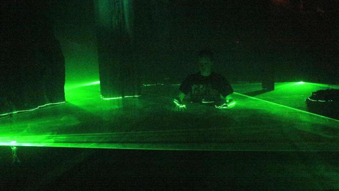 """Kaitlyn Jaffke, marketing and sales coordinator, walks through the """"laser swamp"""" of the """"13th Floor"""" haunted house in Denver"""