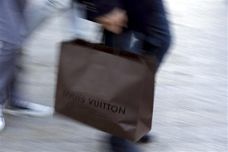 A man walks with a Louis Vuitton shopping bag as he leaves a Louis Vuitton store in Paris