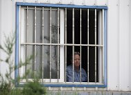 American Chip Starnes, co-owner of Specialty Medical Supplies, looks out from a window after he was held hostage by workers inside his plant at the Jinyurui Science and Technology Park in Qiao Zi township of Huairou District, on the outskirts of Beijing, China Monday, June 24, 2013. An American executive said Monday Starnes has been held hostage for four days at his medical supply plant in Beijing by dozens of workers demanding severance packages like those given to co-workers in a phased-out department. (AP Photo/Andy Wong)