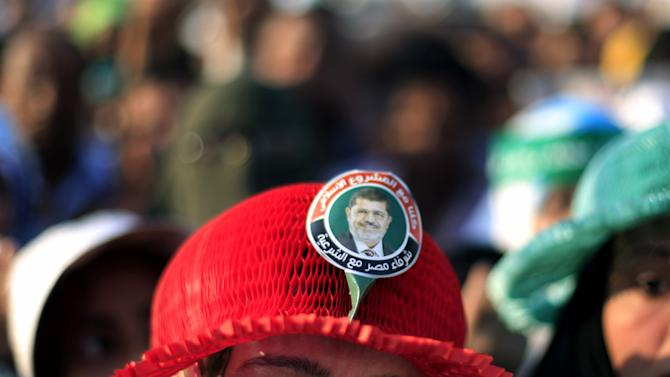 """A Supporter of Egypt's president ohammed Morsi wears a hat with a picture of him and Arabic writing that reads """"all of us with the Islamic project,"""" during a rally in Nasser City in Cairo, Egypt, Friday, June 21, 2013. Tens of thousands of Islamists supporting Egypt's president staged a show of force ahead of massive protests later this month by the opposition, chanting """"Islamic revolution"""" and warning of a new and bloody bout of turmoil. Adding to the combustible mix, the U.S. ambassador in Egypt gets drawn into Egypt's treacherous politics when comments interpreted as critical of the opposition spark outrage, with one activist telling the diplomat to """"shut up and mind your own business.""""(AP Photo/Khalil Hamra)"""