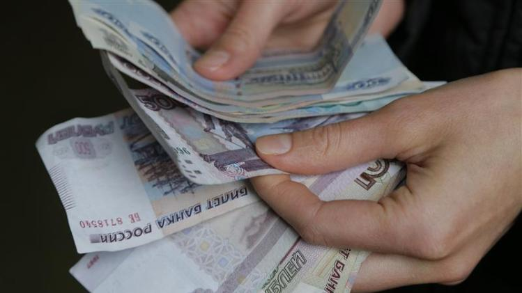 Vendor counts Russian rouble banknotes at a market in Moscow