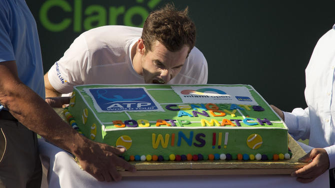 Andy Murray, of Great Britain, poses for photos with the cake he was given for winning his 500th match, after he played Kevin Anderson, of South Africa, at the Miami Open tennis tournament in Key Biscayne, Fla., Tuesday, March 31, 2015. Murray won 6-4, 3-6, 6-3. (AP Photo/J Pat Carter)