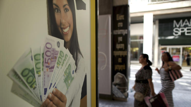 Pedestrians walk outside a pawn shop offering money for gold,  in Athens, on Monday, Aug. 20, 2012.  Greece's finance officials are seeking to finalize euro 11.5 billion in spending cuts necessary for it to continue receiving the international funding that is protecting it from bankruptcy. (AP Photo/Petros Giannakouris)