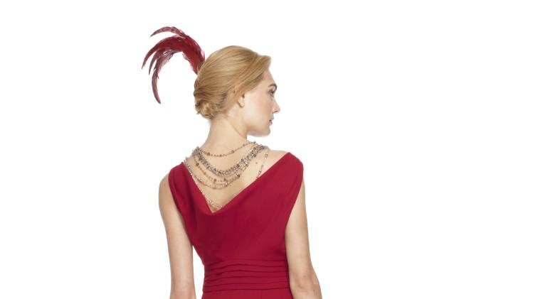 "This image released by Banana Republic shows Crimson Cowl-Back Dress, styled with crystal and topaz layered bead necklaces and a red feather from a limited-edition collection designed by Banana Republic. Led by Creative Director and EVP, Simon Kneen, and styled and curated by ""Anna Karenina"" costume designer Jacqueline Durran, the collection is currently available in Banana Republic stores. (AP Photo/Banana Republic)"