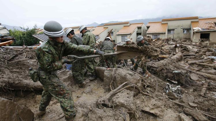 JSDF soldiers search for survivors in the rain at a site where a landslide swept through a residential area at Asaminami ward in Hiroshima