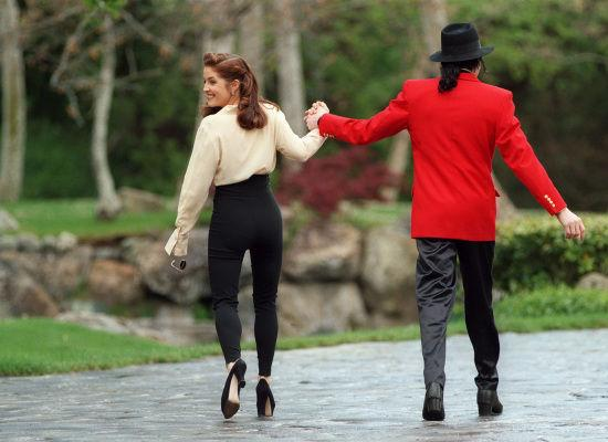 With Lisa Marie Presley in a signature MJ outfit: black hat, satin pants, and oversized red jacket. The two were married from 1994-1996.