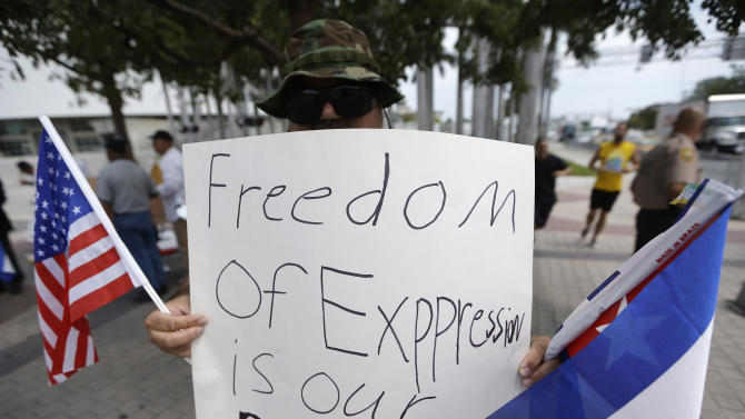 Don Romero holds an American and Cuban flag in support of blogger and activist Yoani Sanchez, of Cuba, before her speech at the Freedom Tower of Miami Dade College, Monday, April 1, 2013, in Miami. Sanchez has gained thousands of followers worldwide for her candid descriptions of modern life in Cuba on her blog Generation Y. (AP Photo/Lynne Sladky)