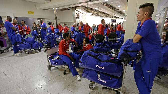 Members of the Cuban Olympic team wait for their ride after arriving at Heathrow Airport Monday, July 16, 2012 as London prepares for the 2012 Summer Olympics. (AP Photo/Charlie Riedel)