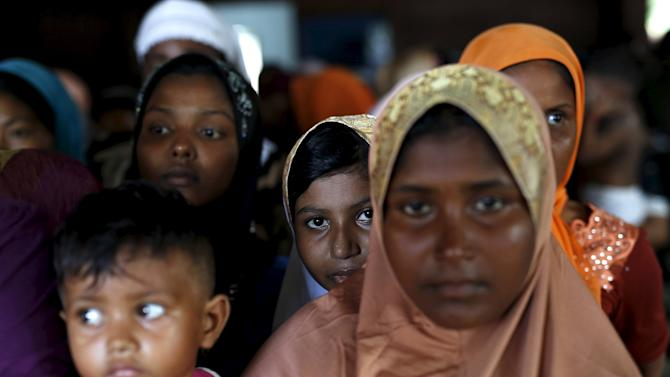 Rohingya migrants  who arrived in Indonesia last week by boat wait in line to receive donations at a temporary shelter in Aceh Timur regency, near Langsa in Indonesia's Aceh Province