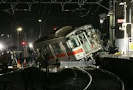 A derailed passenger train of the Sanyo Electric Railway in Takasago city in Hyogo prefecture, western Japan on February 12, 2013. The express passenger train hit a truck at a level crossing in Japan on Tuesday, police said, with footage and reports from the scene showing it had mounted a station platform