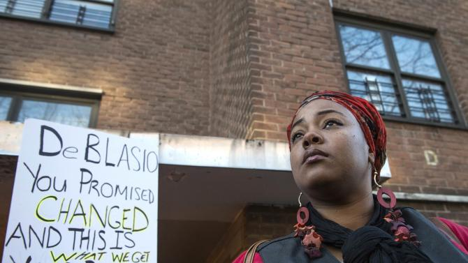 A woman, demanding justice for Akai Gurley, stands near a placard at the site of his shooting death in Brooklyn, New York