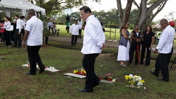Panama's President Juan Carlos Varela looks at the graves of victims of the invasion of Panama at the Jardin de Paz cemetery, during a ceremony in remembrance of the 25th anniversary of the U.S invasion of Panama, in Panama City