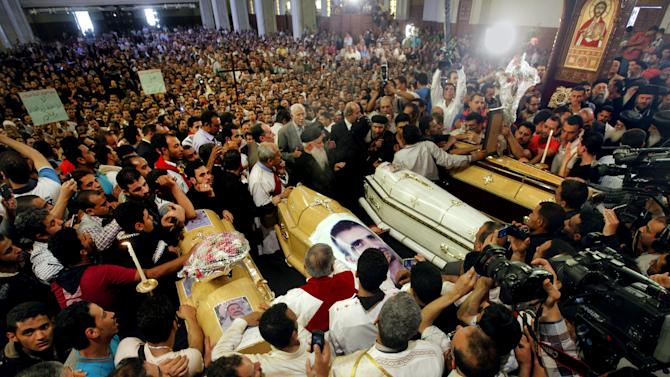 Egyptian Christians gather around four coffins during a funeral service, at the Saint Mark Coptic cathedral in Cairo, Egypt, Sunday, April 7, 2013. Several Egyptians including 4 Christians and a Muslim were killed in sectarian clashes before dawn in Qalubiya, just outside of Cairo on Saturday, April 6, 2013. (AP Photo/Amr Nabil)