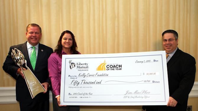 IMAGE DISTRIBUTED FOR LIBERTY MUTUAL INSURANCE - Notre Dame Coach Brian Kelly was named Liberty Mutual Coach of the Year Monday  prior to the National Championship Game. The award includes a $50,000 donation to charity, which will support the Kelly Cares foundation. Presenting the donation to Coach Kelly and his wife, Paqui, is Liberty Mutual Insurance Chief Marketing Officer James MacPhee (R). Liberty Mutual also will donate a $20,000 scholarship to the Notre Dame Alumni Association. The other 2012 Liberty Mutual Coach of the Year Award winners, also receiving donations for charity and scholarship, are Willie Fritz, Sam Houston State, Peter Rossomando, New Haven, and Glenn Caruso, St. Thomas, at the 2012 Liberty Mutual Coach of the Year Award Winners Announcement, on Monday, Jan. 7, 2013 in Ft. Lauderdale, Fla. (Photo by Marc Serota/Invision for Liberty Mutual Insurance/AP Images)