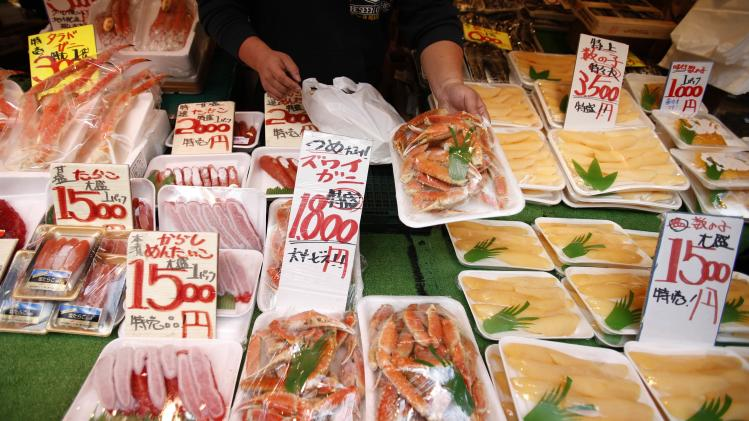 A shopkeeper shows a pack of frozen crabs to shoppers at a shopping district in Tokyo