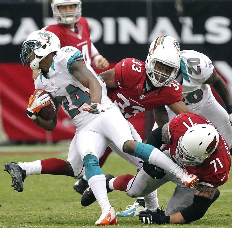 Miami Dolphins cornerback Sean Smith (24) is tackled by Arizona Cardinals guard Daryn Colledge (71) and William Powell (33) after running back an interception during the first half of an NFL football game, Sunday, Sept. 30, 2012, in Glendale, Ariz. (AP Photo/Paul Connors)