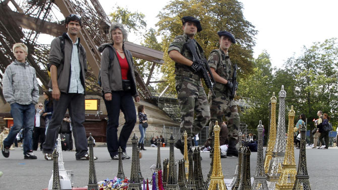 French soldiers patrol the area under the Eiffel Tower and walk past replicas for sale, in Paris, Sunday, Oct. 3, 2010. The State Department plans to caution Americans traveling in Europe to be vigilant because of heightened concerns about a potential al-Qaida terrorist attack aimed at U.S. citizens and Europeans. The travel alert expected to come out Sunday is for travelers' guidance, is general in nature and isn't intended to focus on any specific country, location or tourist sites. (AP Photo/Laurent Cipriani)