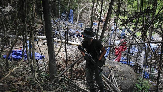 A member of the Malaysian General Operation Force stands guard at an abandoned camp found in Wang Burma at the Malaysia-Thailand border outside Wang Kelian, Malaysia on Tuesday, May 26, 2015. Malaysian forensic teams exhumed a body at an abandoned camp on Tuesday that was used by human traffickers, the first of what police predicted would be more grim findings as they combed through a cluster of jungle camps on the border with Thailand. (AP Photo/Joshua Paul)