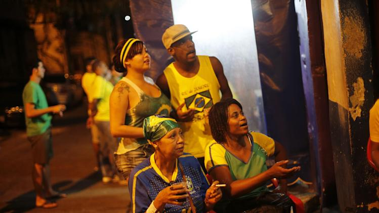 Brazil fans watch the game against Cameroon during the 2014 soccer World Cup at the Cantagalo favela in Rio de Janeiro, Brazil, Monday, June 23, 2014. Brazil's Neymar scored twice in the first half to lead Brazil to a 4-1 win over Cameroon on Monday, helping the hosts secure a spot in the second round of the World Cup