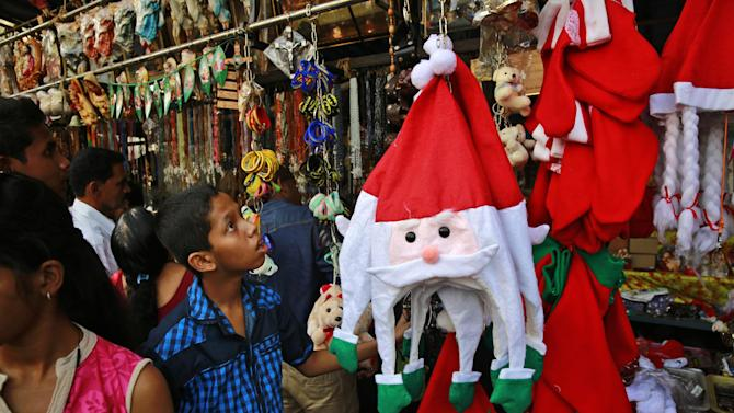 An Indian boy looks at Santa Claus hats on display for sale at a roadside stall outside a church on Christmas Day in Mumbai, India, Thursday, Dec. 25, 2014. Christians make up about 2 percent of the population in India, a secular country of more than 1 billion people where Hindus form the overwhelming majority. (AP Photo/Rafiq Maqbool)