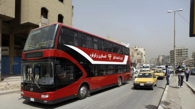 A double-decker bus is seen in downtown Baghdad, Iraq, Wednesday, May 30, 2012. Iraqis are hailing the return of red double-decker buses to Baghdad's streets, a sign that the country is trying to restore some normalcy after a decade of war, sanctions and sectarian violence. (AP Photo/Khalid Mohammed)
