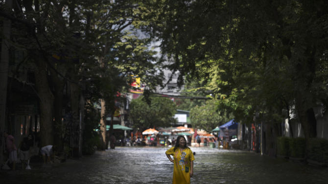 A Thai woman stands in the middle of a flooded street in Bangkok, Thailand, Saturday, Oct. 29, 2011. Defenses shielding the center of Thailand's capital from the worst floods in nearly 60 years mostly held at critical peak tides Saturday, but areas along the city's outskirts remained submerged along with much of the countryside. (AP Photo/Altaf Qadri)
