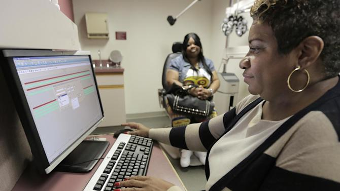 """In this Sept. 5, 2013, Jacqueline Saulsberry, a service coordinator at the Illinois Eye Institute, gathers information from patient Shameka Lewis-Coolidge during an appointment in Chicago. With the program known as """"Obamacare"""" only weeks away from its key launch date, hectic preparations are now in motion in communities across the country to deal with one of its major practical challenges: hiring and training a small army of instant experts who can explain the intricacies of health insurance to people who've never had it. More than 100 nonprofits and related organizations have been recruited by the federal government to sign up """"navigators"""" who can help the 30 million uninsured people who can now gain coverage. (AP Photo/M. Spencer Green)"""